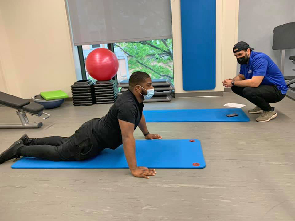 A picture of a trainer from the Healthplex Fitness Center training a member to do a stretching exercise on the floor.