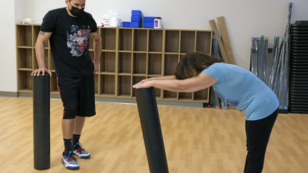 A picture of a trainer from the Healthplex Fitness Center training a member to do a core and stretching exercise on the floor.